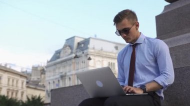 Man works with a laptop sitting on the street