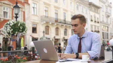 Man works with a laptop sitting in cafe on the street