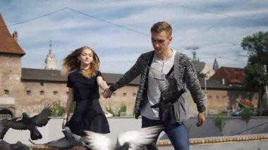 Happy couple runs across the square