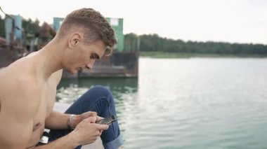 Man sits on the bay with his phone