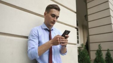 Young man checks his phone standing on the street