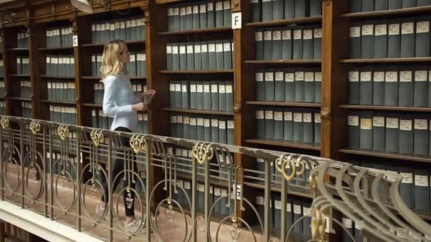 Student bere knihu z police v knihovně
