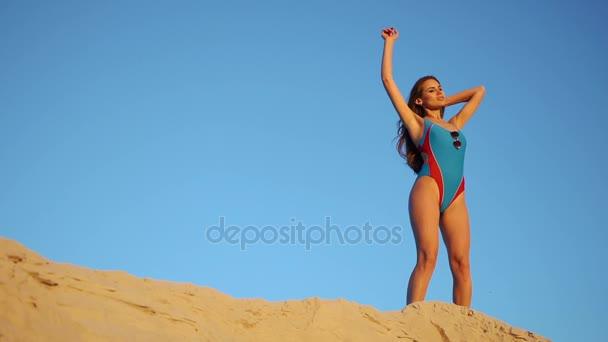 0516dfa90a39 Mujer en traje de baño azul camina sobre la duna de arena en la noche