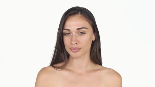 Splendida giovane donna con i capelli lunghi e le lentiggini con pose le spalle nude per una fotocamera