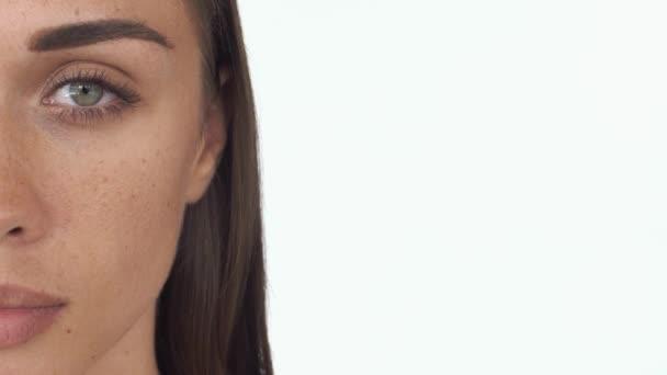 Polovina tváře Zenske s tmavě zelené oči a pihy na bílém pozadí