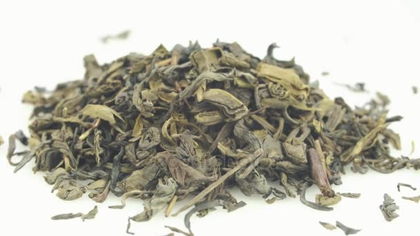 Száraz zöld tea fekszik az asztalon. A keret óramutató járásával megegyezően.