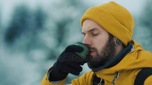 Krásné hory v zimním období. Muž s plnovousem, žlutá zimní oblečení je pít horký čaj nebo kávu venku v chladu.