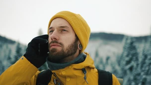 Muž s plnovousem, žlutá zimní oblečení mluvil po telefonu. Turista jede v zimních horách s batohem. Krásné hory v zimě