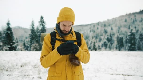 Muž s plnovousem, žlutá zimní oblečení pomocí telefonu. Turista jede v zimních horách s batohem. Krásné hory v zimě