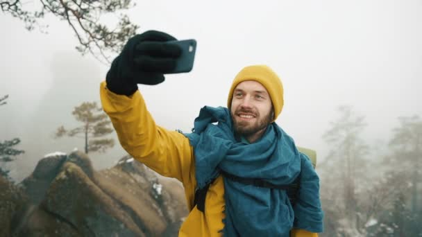Krásné hory v zimním období. Muž s plnovousem, žlutá zimní oblečení se selfie na pozadí hory.