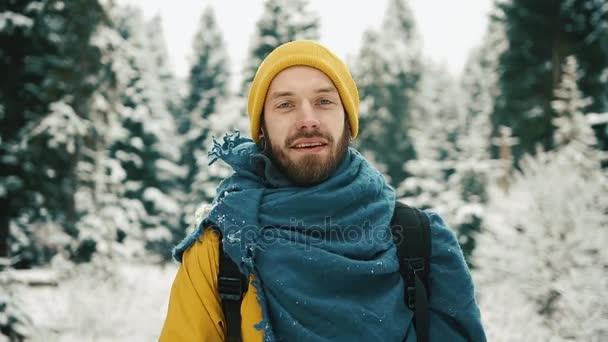 Krásné hory v zimním období. Muž s plnovousem, žlutá zimní oblečení jde dolů horské silnici a při pohledu na fotoaparát