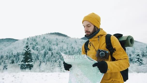 Krásné hory v zimním období. Chlap s plnovousem, žlutá zimní oblečení je putování a drží mapu v jeho rukou, na pozadí zimní krajiny