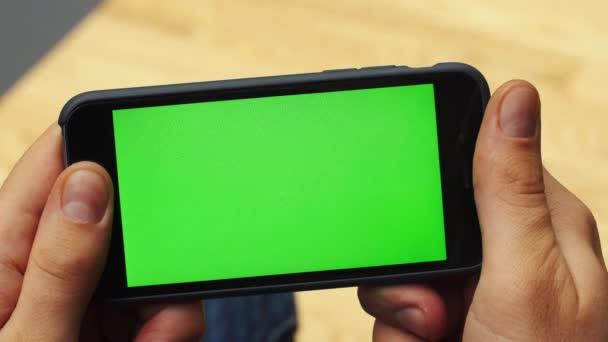 Uomo che usando smartphone orizzontale con lo schermo verde. Close-up shot di equipaggia le mani con il telefono cellulare. Chiave di crominanza. Chiuda in su. Orizzontale