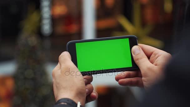 Muž vodorovnou smartphone pomocí zeleným plátnem. Close-up shot mans rukou s mobilním telefonem. Chromatický klíč. Zblízka. Horizontální