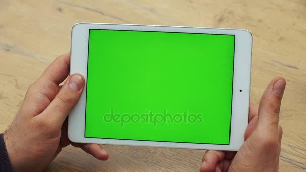 Muž, horizontální tabletu pomocí zeleným plátnem. Close-up shot mans rukou s tabletem. Chromatický klíč. Zblízka. Horizontální