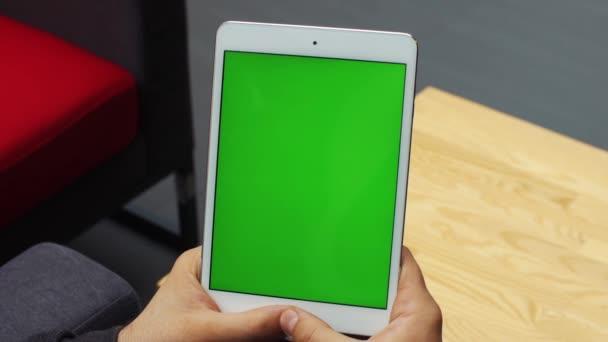 Muž, vertikální tabletu pomocí zeleným plátnem. Close-up shot mans rukou s tabletem. Chromatický klíč. Zblízka. Vertikální