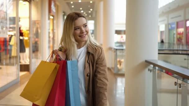 Šťastné blond žena se dívá na její barevné papírové sáčky stojí v nákupní centrum