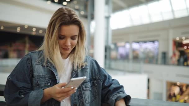 Mladá žena usměje a typy něco v jejím postavení smartphone s taškami v nákupní centrum