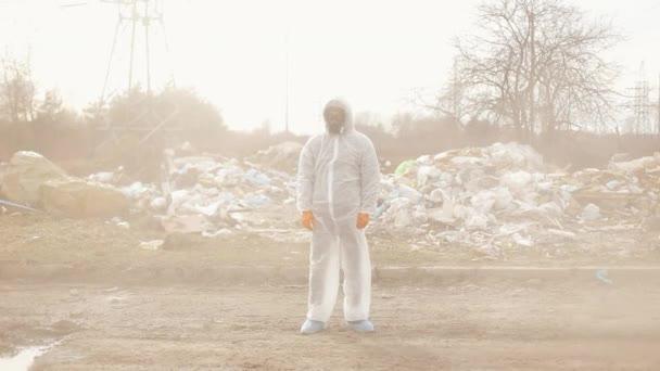 Virologe Mann in Schutzanzug und Atemschutzmaske blickt in Kamera auf Deponieverschmutzung, Umweltkatastrophe