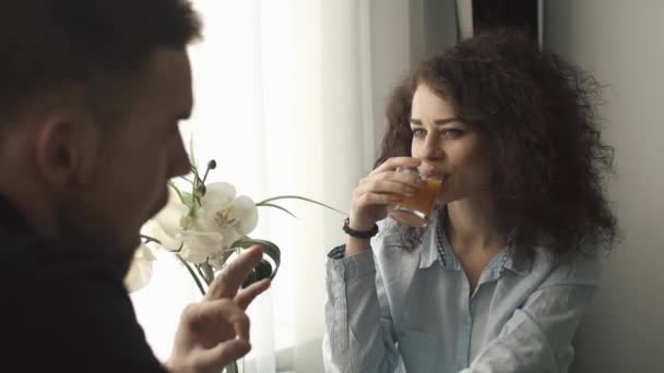 Man and charming curly woman sit before bright window