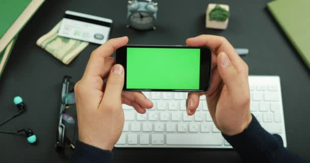 Man holds a black smartphone with green screen over a working table and scrolls something on it