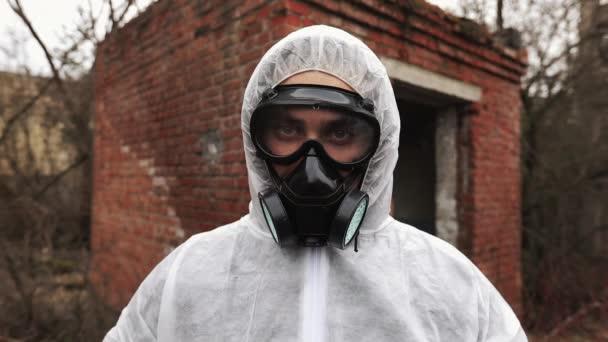 Mann im Bio-Gefahrenanzug und Gasmaske blickt direkt in die Kamera
