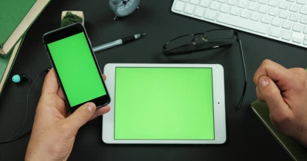 Mann hält Smartphone mit grünen Bildschirm über einen Tisch mit Greenscreen und scrollt etwas darauf