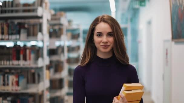 Dívka s dlouhými vlasy vypadá přímo do kamery a procházky podél police v knihovně