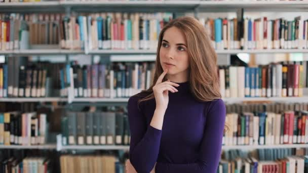 Thoughtful young woman stands before the shelves in the library