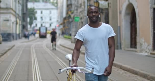 Handsome African American Young Man in Headphones Looking around and Pushing the Stylish Modern Bike while Walking Down Old Busy City Street. Tourist Concept.