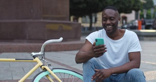 Kulaklıklı Afro-Amerikalı Heyecanlı Adam 'ın Smartphone' uyla görüntülü telefon görüşmesi ve sohbeti. Şehir Arkaplanındaki Stylish Bisikleti 'nin yakınındaki basamaklarda oturan adam gülüyor..