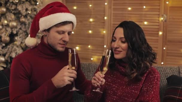 glückliches junges Paar, das auf dem Sofa in der Nähe des Weihnachtsbaums vor heimischem Hintergrund sitzt, Sektgläser klimpert und Küsse trinkt. Urlaubs- und Neujahrskonzept hautnah.