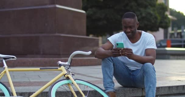 gut - schaut afrikanisch-amerikanischer junger Kerl mit seinem Smartphone, tippt Nachrichten, sieht aufgeregt aus, während er auf der Treppe neben stilvollem Fahrrad im Hintergrund der Stadt sitzt. Frontansicht.