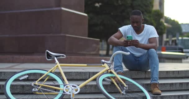 Handsome Young African American Guyin Casual Clothes Using his Smartphone with Serious Face Expression while Sitting on Steps near Stylish Bike at City Background