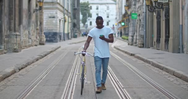 Handsome Muscular African American Young Man In Casual Clothes Using his Smartphone and Pushing the Stylish Modern Bike while Walking Down Old Town Street. Tourist Concept.