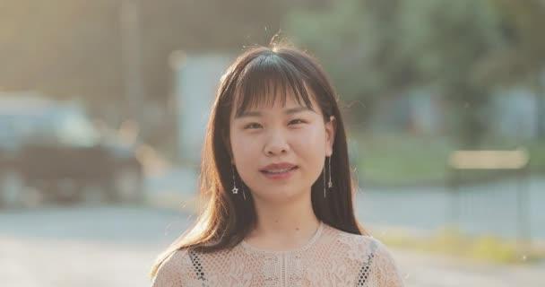 Zblízka asijské ženy s zářivým úsměvem.