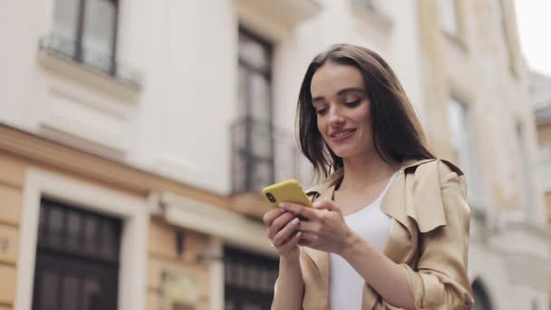 Blick von unten auf eine glückliche junge schöne Frau, die auf der Straße steht und auf ihrem Smartphone tippt.