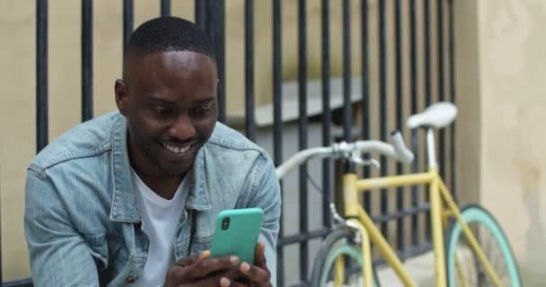 fröhlicher afrikanisch-amerikanischer junger Mann, der mit seinem Smartphone SMS tippt, aufgeregt und lachend neben einem stylischen Fahrrad mit altem Metallzaun im Hintergrund sitzt.