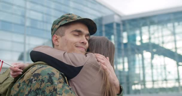 Close up of military man embracing wife.