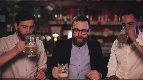 Cheerful male friends in good mood drinking beer and resting after work day. Three colleagues talking and laughing while sitting and having great time at pub. Concept of leisure.