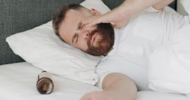 Fiatal szakállas férfi felébred, miközben az ágyban fekszik üres üveggel a feje mellett. A 30-as éveiben járó fickó rosszul érzi magát, és fáj a feje, miután egész éjjel ivott és bulizott..