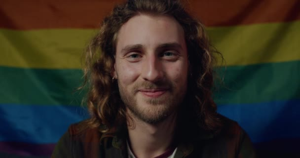 Portrait of cheerful millennial guy with earings looking to camera. Close up view of young handsome man with long wavy hair smiling, posing with rainbow flag at background. Concept of pride.