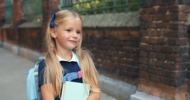 Malá roztomilá holčička s knihou při procházce po ulici. Pěkné malé dítě s dlouhými blond vlasy a taškou na zádech, jak pomalu chodí do školy. Pojem děti a vzdělání. Venku.