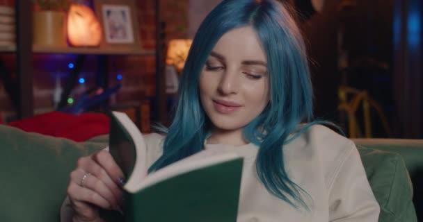 Közelről kilátás csinos fiatal nő kék haj olvasás irodalom.Millenniumi lány élvezi a könyvet, és mosolyog, miközben ül a kanapén otthon. A szabadidő és a szórakozás fogalma.