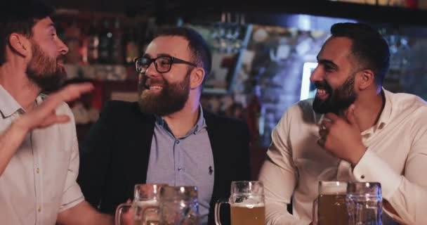 London UK - 19 April 2019: Happy bearded guys having good mood while spending time together at pub. Close up view of male friends laughing and talking while drinking beer and cheering.