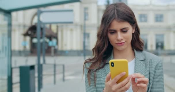 Großaufnahme einer konzentrierten jungen Frau, die an der Stadtstraße scrollt und den Telefonbildschirm berührt. Millennial Mädchen mit ihrem Smartphone und dem Surfen im Internet, während sie lächelt und geht. Draußen.