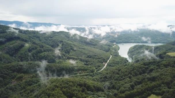 Mraky mlhy po letním dešti. Letní krajina s jezerem a horským lesem. Letecký pohled na nádrž / jezero Starina, Národní park Poloniny, Slovensko.