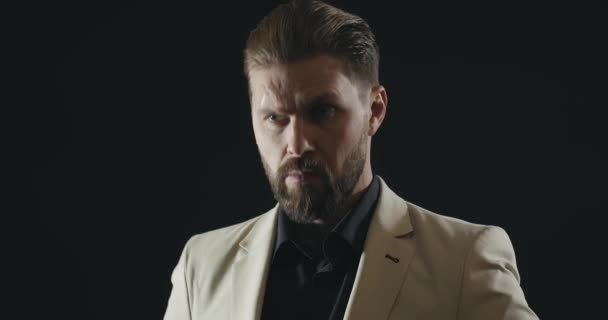 Elegantní muž v bílém obleku izolovaný na černém