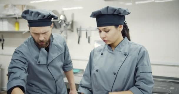kompetente Köchin und männliche Assistentin in der Küche
