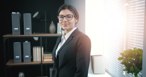 Vidám nő sötét hajjal a modern irodában